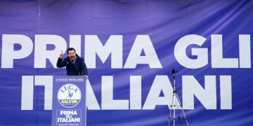 "Italian Northern League leader Matteo Salvini speaks during a political rally with a banner reading ""Italian first"" in the back in Milan"